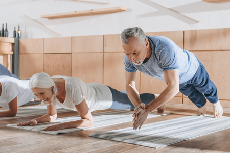 group of senior people doing plank on yoga mats in studio Stok Fotoğraf
