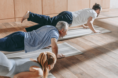 group of people practicing yoga on mats in studio Stock Photo