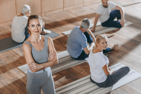 high angle view of female instructor looking at camera while senior people exercising on yoga mats Stock fotó