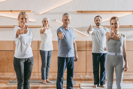 senior people and instructor in sportswear showing thumbs up and smiling at camera in fitness studio