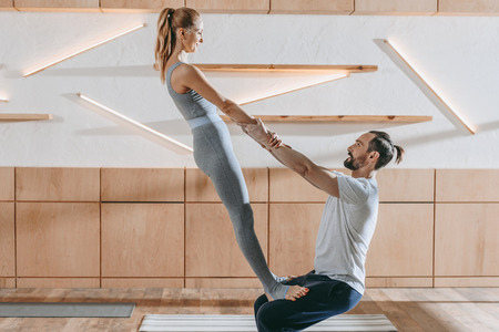 middle aged couple practicing yoga together at training class Stock Photo
