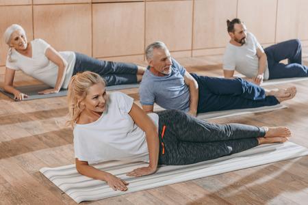 smiling senior people training on yoga mats at training class