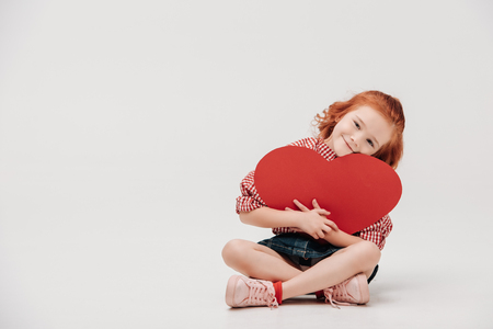 adorable little child hugging red heart symbol and smiling at camera isolated on grey
