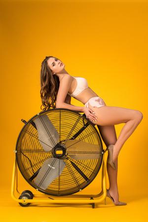 sexy girl in lingerie set leaning on fan on orange Imagens