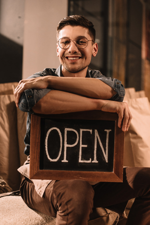 portrait of smiling coffee shop worker with open sign looking at camera Foto de archivo