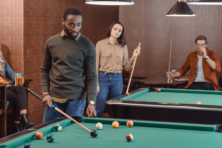 african american man playing in pool at bar with friends