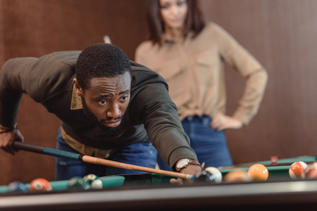african american man playing in pool at bar