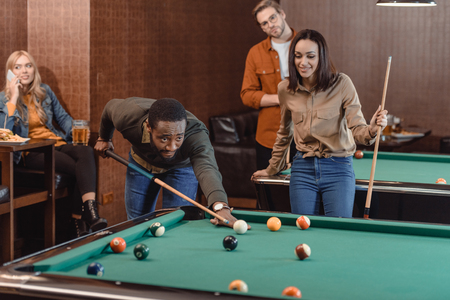 young successful multiethnic friends playing in pool at bar Imagens