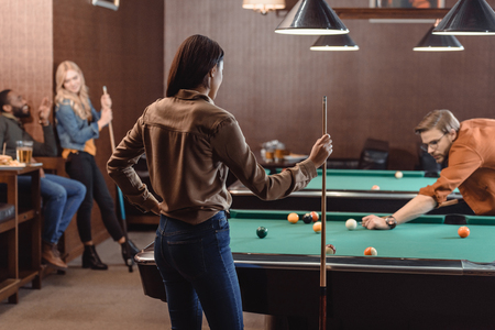 young successful multiethnic friends playing in pool at bar Banque d'images