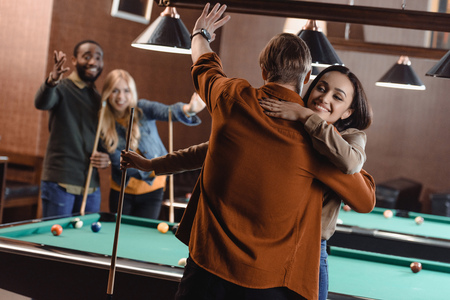 back view of young friends hugging beside pool table at bar