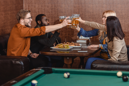 company of multiethnic friends eating and drinking beside pool table at bar