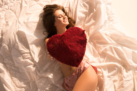 top view of smiling girl lying in underwear with heart shaped pillow Imagens