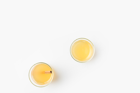 top view of glasses of apple cider with cinnamon stick isolated on white