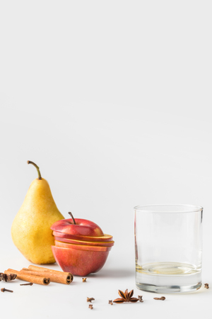 empty glass with apple and pear on white surface