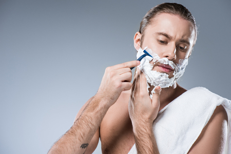 Young caucasian man with shaving foam on face holding razor in hand against his cheek, while bath towel laying on his shoulder, isolated on gray