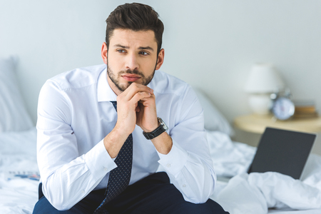 handsome thoughtful businessman in white shirt and tie sitting on bed