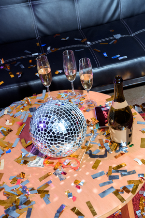 close up view of champagne and disco ball on table in party room Archivio Fotografico