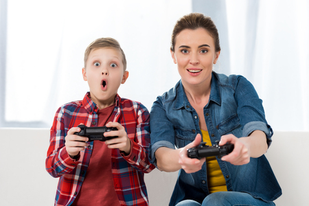 surprised mother and son playing video games with gamepads together and looking at camera