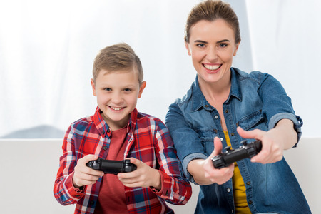 excited mother and son playing video games with gamepads together
