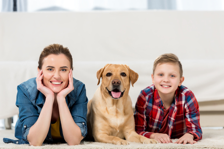 happy mother and son lying on floor with their dog and looking at camera