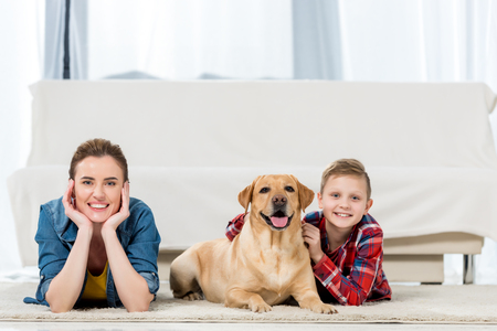 beautiful mother and son lying on floor with their dog and looking at camera