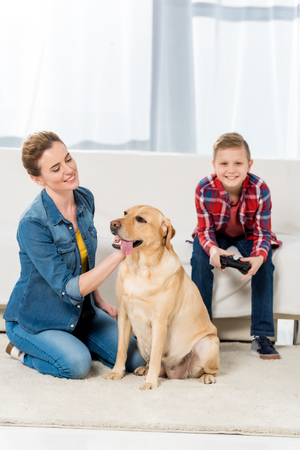 happy mother petting dog while son playing video games
