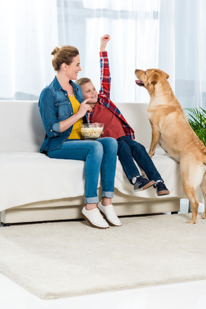 mother and son feeding their dog with popcorn