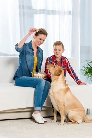 happy mother and son feeding their dog with popcorn