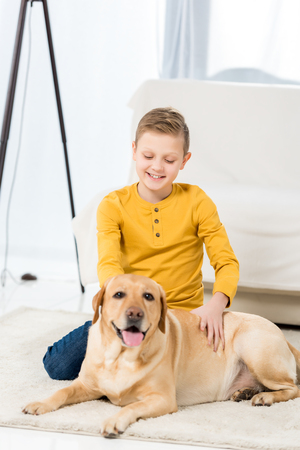 happy little kid petting his dog while sitting on floor Stock Photo