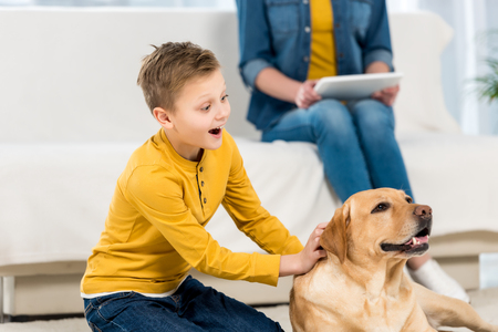 excited little kid petting dog on floor while mother using tablet on couch