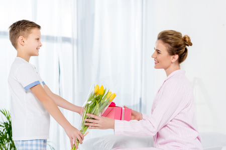 son presenting gift and tulips bouquet for mother on mothers day morning
