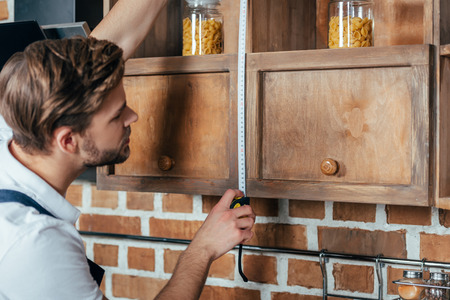 side view of young handyman measuring kitchen furniture with tape