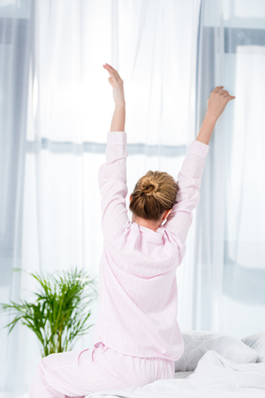 rear view of woman stretching after wake up Banco de Imagens