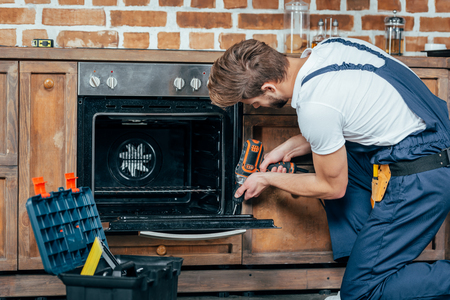 young repairman in protective workwear fixing oven with electric drill