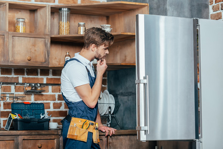 young repairman with tool belt looking at broken refrigerator