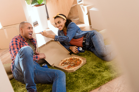 african american couple eating pizza in new apartment with cardboard boxes