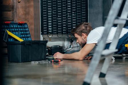 selective focus of young foreman fixing refrigerator Reklamní fotografie