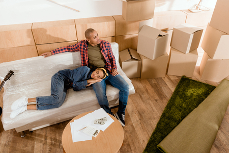 african american couple resting in new apartment with cardboard boxes Stock Photo