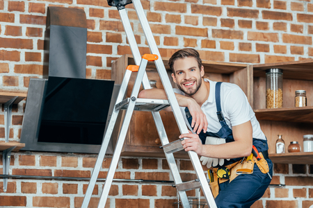 handsome young foreman standing on ladder and smiling at camera while fixing kitchen hood