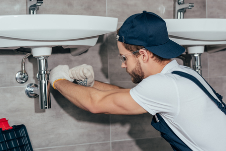 close-up view of young professional plumber fixing sink in bathroom