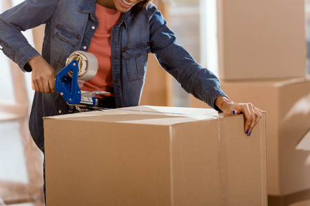 cropped view of african american woman packing cardboard box with tape