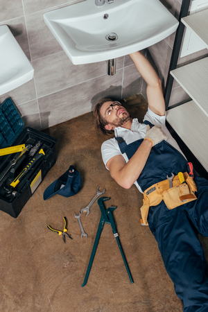high angle view of young male plumber fixing sink in bathroom Stock Photo