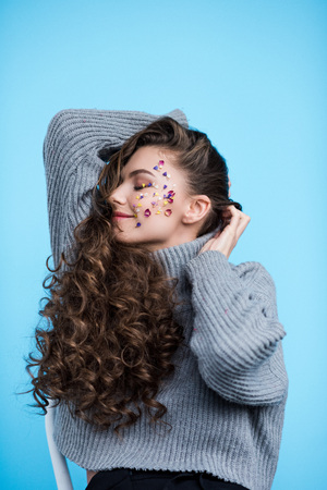 happy young woman with flower petals on face in sweater isolated on blue