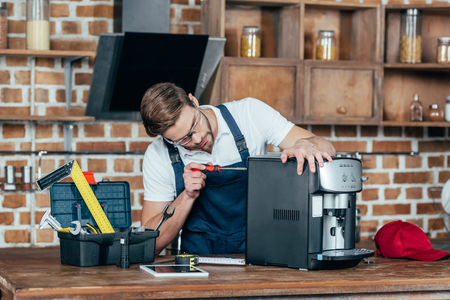 professional young worker in eyeglasses and protective workwear fixing coffee machine Reklamní fotografie
