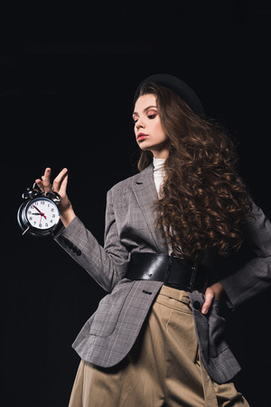elegant fashionable young woman holding clock isolated on black