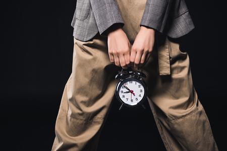cropped shot of stylish woman holding clock isolated on black