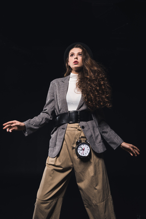 low angle view of fashionable shocked young woman with clock looking away isolated on black
