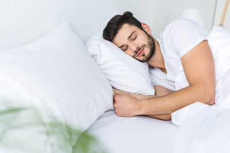 bearded man sleeping on bed in bedroom