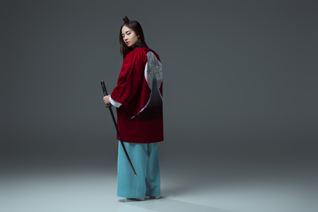 back view of samurai in kimono holding katana and looking at camera on grey Banco de Imagens