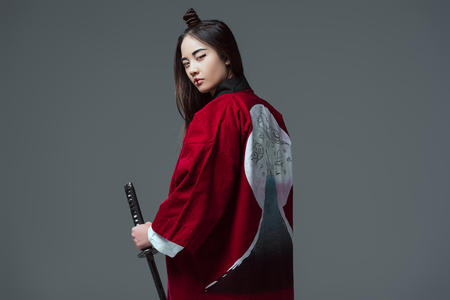 young woman in traditional japanese kimono holding katana and looking at camera isolated on grey 版權商用圖片